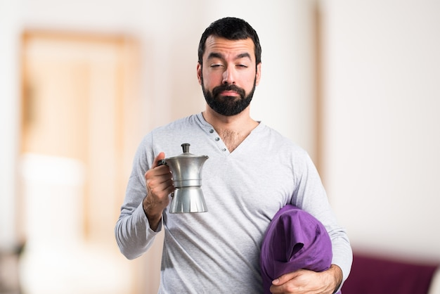 Man in pajamas holding a coffee pot Free Photo