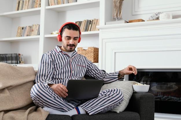Uomo in pigiama trascorrere del tempo divertente sul laptop Foto Gratuite