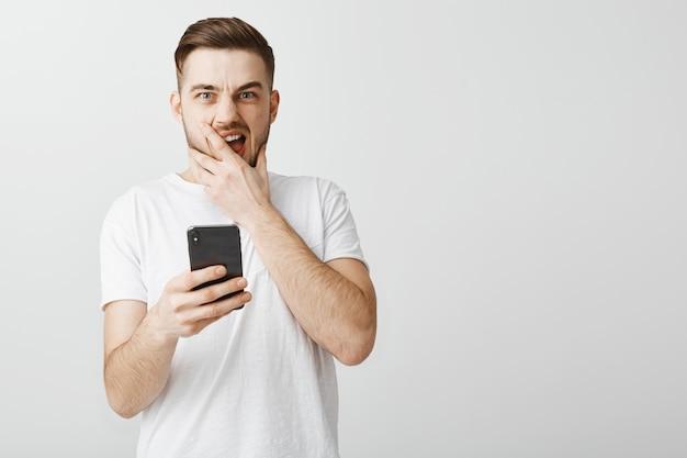 Uomo in preda al panico che tiene il telefono cellulare e si occupa di aver commesso un errore Foto Gratuite