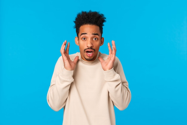 Man in panic telling something terrible, bad news. alarmed, scared, shocked african-american guy witness accident, raising hands near face frightened and startled, gasping concerned, blue Premium Photo