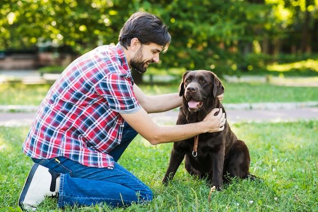 彼の犬を公園に叩く男 無料写真