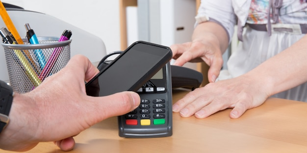Man paying with mobile phone in shop Premium Photo