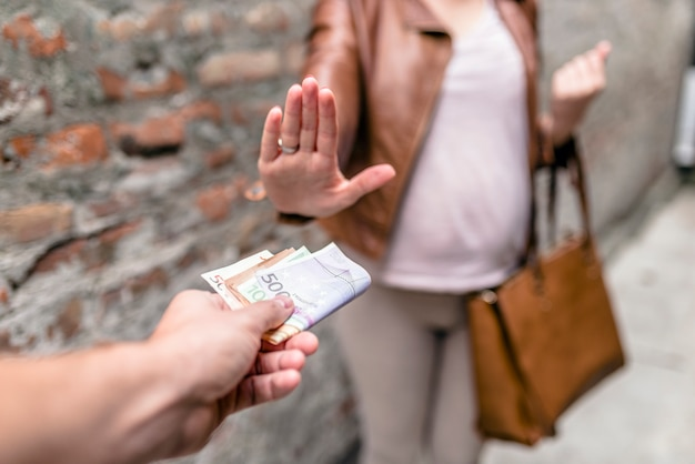 Man paying woman for sex. woman refusing to take bribe, concept of corruption and bribery Premium Photo
