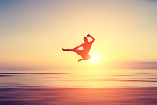 Man performing high kick on the beach Premium Photo
