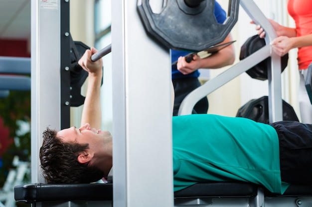 Man and personal trainer in gym Premium Photo