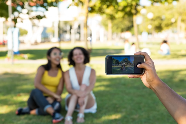 Man photographing female friends in park Free Photo