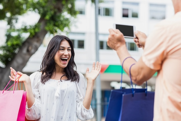 Man photographing smiling woman with shopping bag Premium Photo