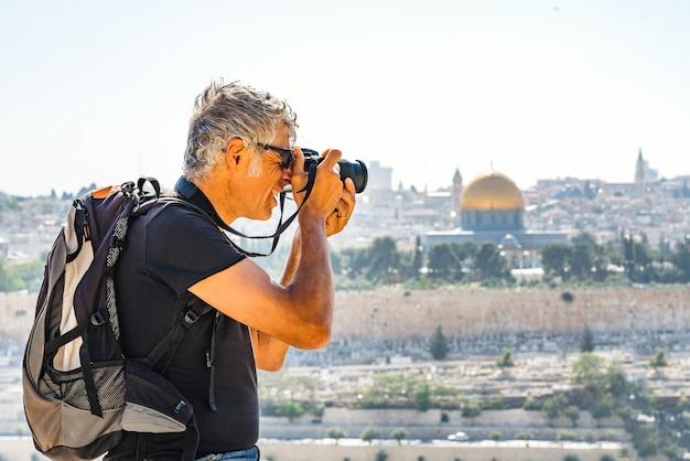 Человек фотографирует туристов в иерусалиме Premium Фотографии