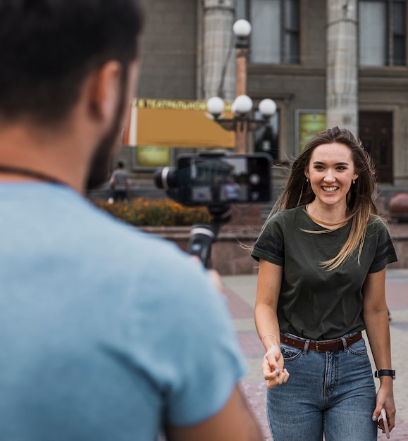 Man photographing woman with phone Free Photo