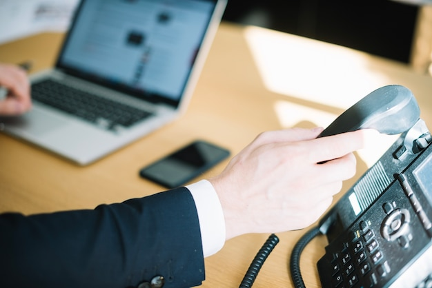 Man picking up phone in office Free Photo