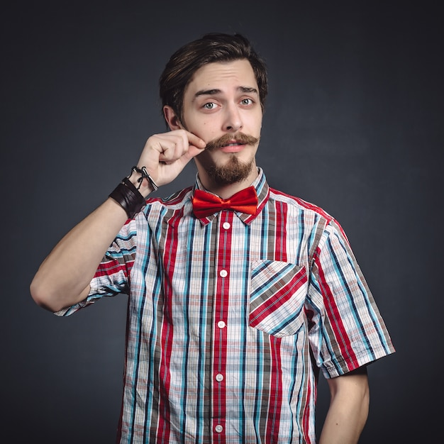 Man in plaid shirt and bow tie in the studio Free Photo