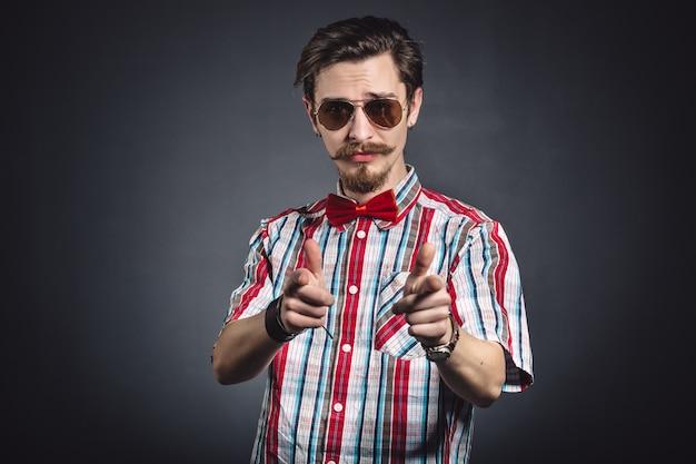 Uomo in camicia a quadri e farfallino con gli occhiali in studio Foto Gratuite
