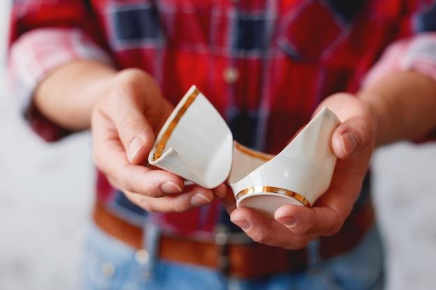 Man in plaid tartan shirt holds a broken white cup. Premium Photo