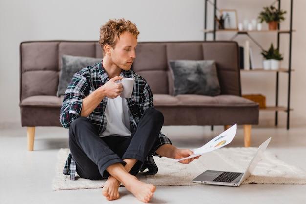 Uomo che pianifica di ridipingere la casa mentre beve il caffè Foto Gratuite