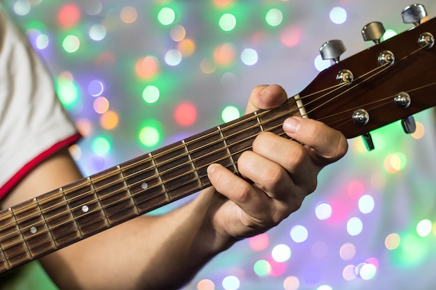 Man playing on acoustic guitar, closeup fingers on guitar neck against christmas blurred bokeh lights on background Premium Photo