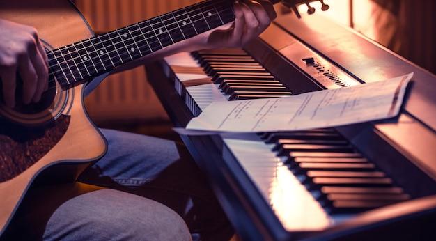 Uomo che suona la chitarra acustica e il piano in primo piano, note di registrazione, bel colore di sfondo, concetto di attività musicale Foto Gratuite