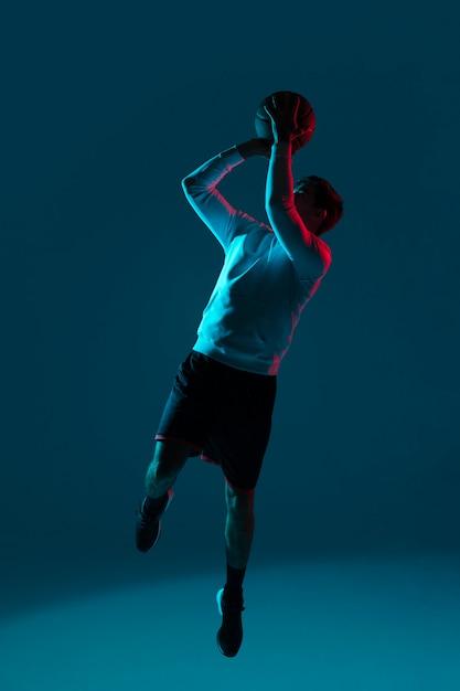 Человек играет в баскетбол с холодными огнями Бесплатные Фотографии