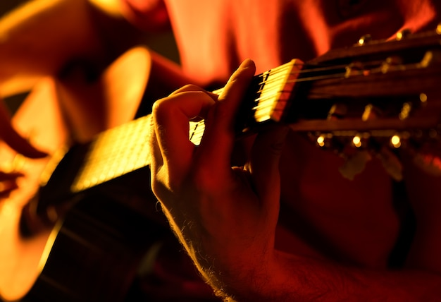Man playing classic guitar on a stage musical concert close-up view Free Photo
