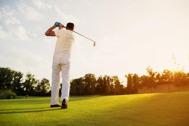 Man playing golf taking swing shot on a lawn. Premium Photo