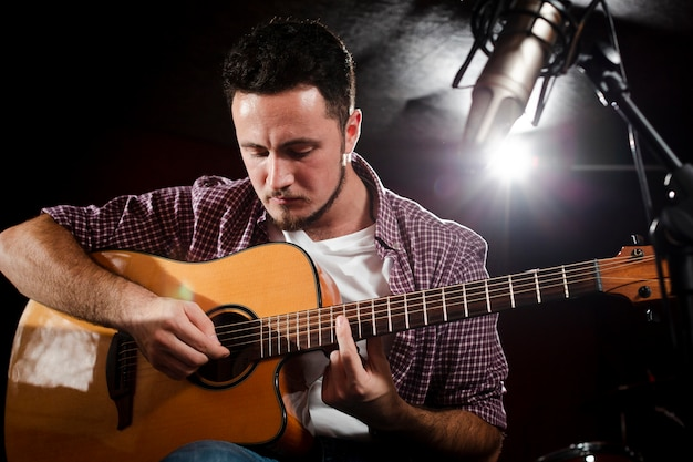 Man playing guitar and defocused microphone Free Photo
