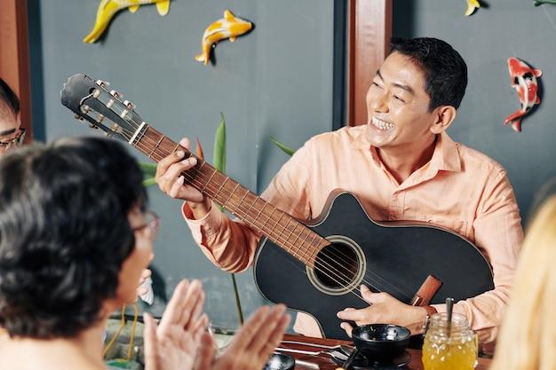 Человек играет на гитаре для друзей и родственников Premium Фотографии