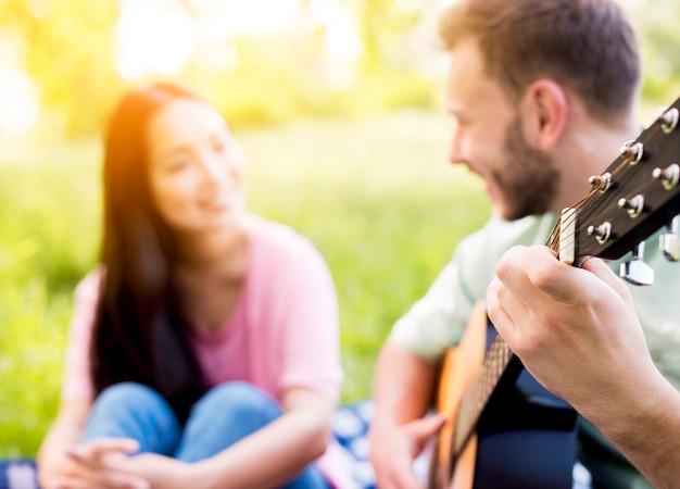 Man playing guitar on picnic Free Photo