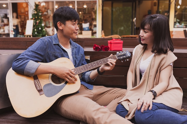 Man playing a guitar while looking at his girlfriend with a gift and a flower Free Photo
