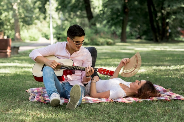 Man playing the guitar to a woman Free Photo