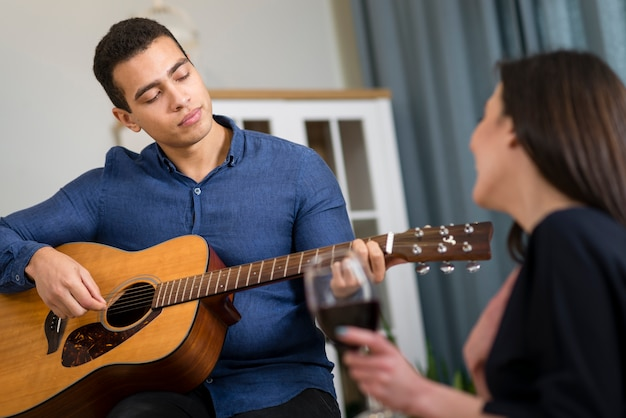 Man playing a song for his girlfriend Free Photo