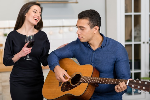 Man playing a song for his wife Free Photo