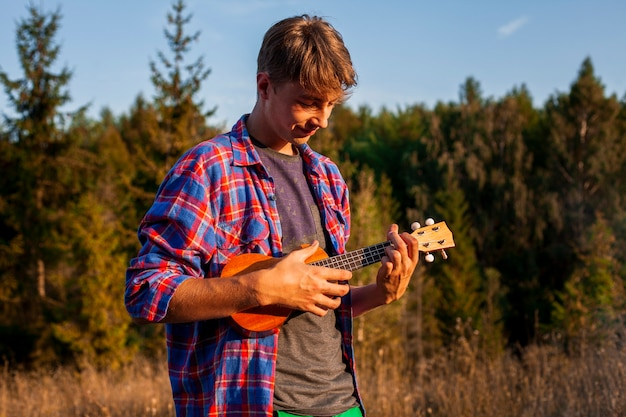 Man playing ukulele in the forest Free Photo