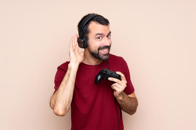 Человек играет с контроллером видеоигры над изолированной стеной, слушая что-то, положив руку на ухо Premium Фотографии