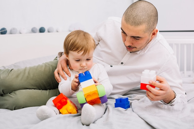 Man playing with little baby holding toy building blocks Free Photo