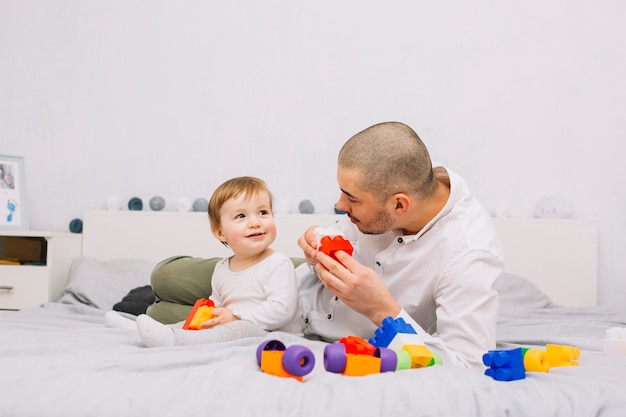 Man playing with smiling little baby with toy building blocks Free Photo