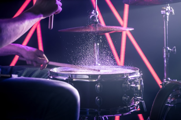 The man plays the drums, on the background of colored lights Free Photo