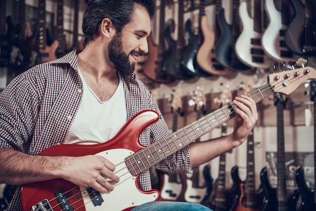 Man plays electric guitar in musical instrument store Premium Photo