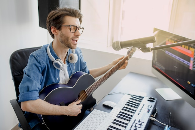 Man plays guitar and singing and produce electronic soundtrack or track in project at home. male music arranger composing song on midi piano and audio equipment in digital recording studio. Premium Photo