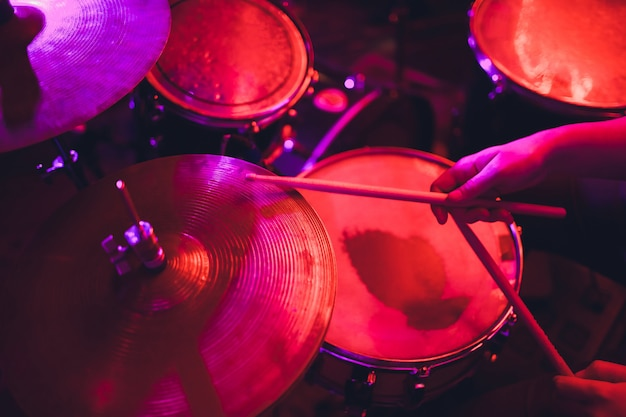 Man plays musical percussion instrument with sticks closeup on black Premium Photo