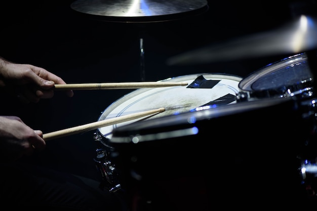 Man plays musical percussion instrument with sticks closeup, a musical concept with the working drum, beautiful lighting on the stage Premium Photo