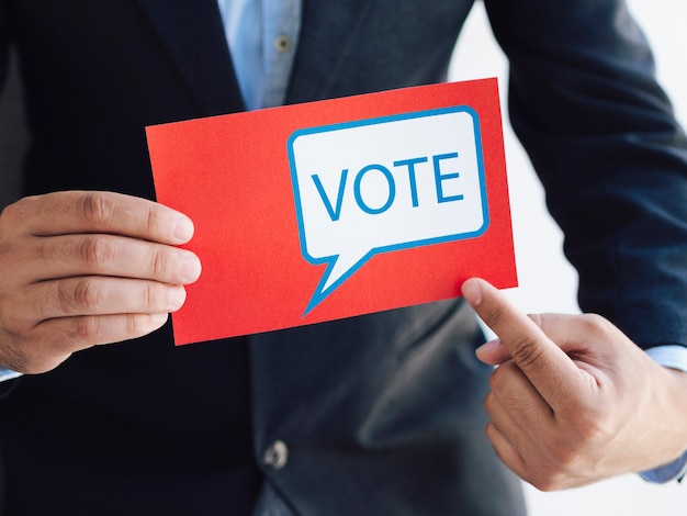 Man pointing to a ballot with a voting message Free Photo