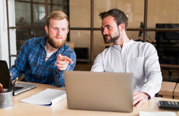 Man pointing finger at his colleague's laptop at workplace Free Photo
