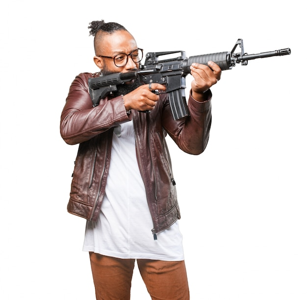 Man pointing to his side with machine gun Free Photo