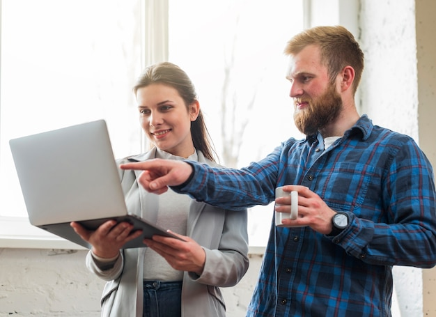 Man pointing at laptop hold by his female colleague Free Photo