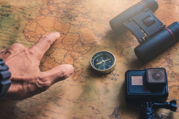 Man pointing notepad for note with binoculars pencil, compass on paper map for travel adventure discovery image Premium Photo