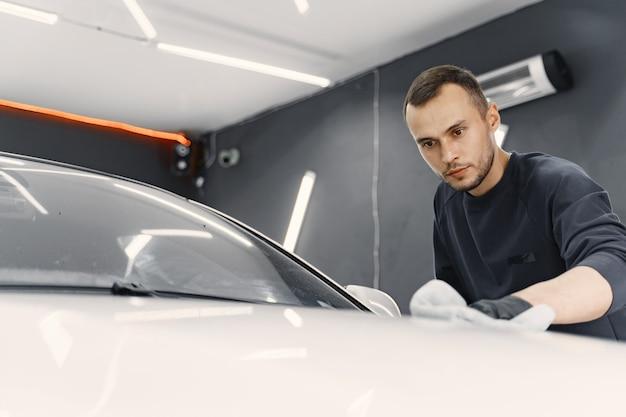 Человек полирует машину в гараже Бесплатные Фотографии