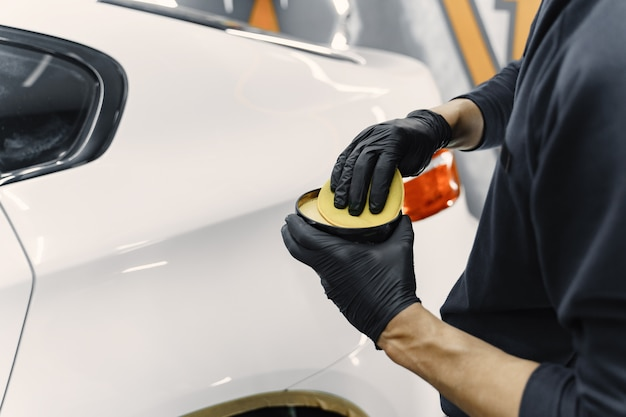 Man polish a car in a garage Free Photo