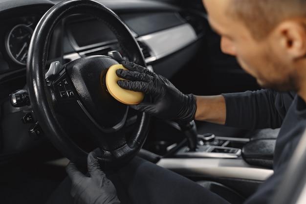 Man polish salon of car in a garage Free Photo