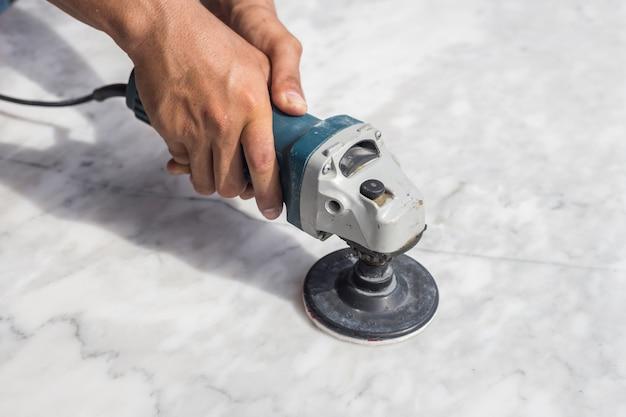 Человек, полирующий мраморный каменный стол маленькой угловой шлифовальной машиной Premium Фотографии