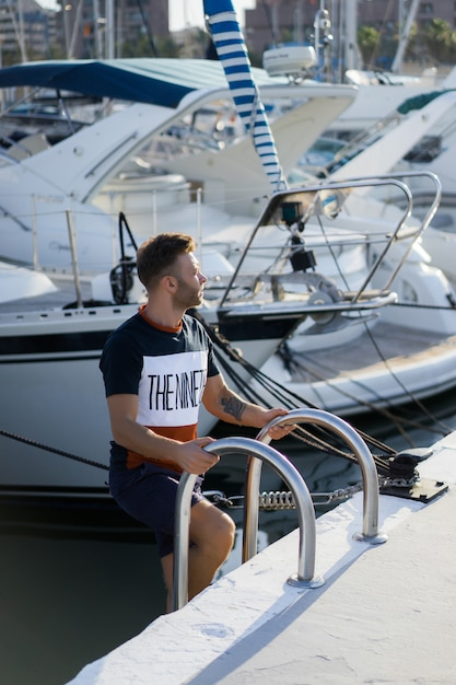 A man in the port preparing the yacht for the trip Free Photo