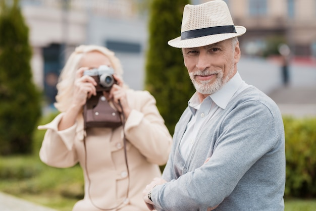 Man posing in hat. woman take pictures on camera. Premium Photo